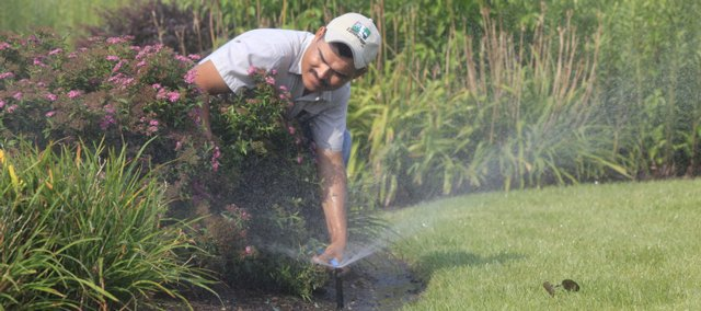 Miguel Martinez, who works for Lawrence Landscape, adjusts some sprinklers at the Free State Business Center at 1201 Wakarusa Drive. New technological advances can ensure you're not wasting water and money on your home or commercial lawn care.
