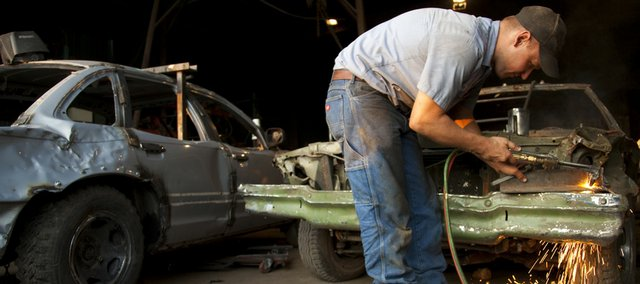 Richard Neis, who plans to compete in tonight's demolition derby at the Douglas County Fair, welds a battery housing for his 1995 Crown Victoria derby car, at left. Neis worked Wednesday in his parents' garage in Eudora. He has participated in the derby for the last nine years.
