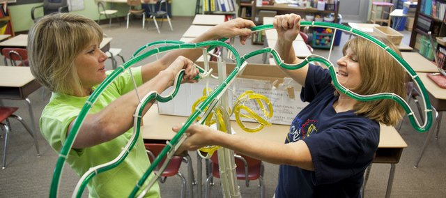 Fourth-grade teachers Melissa Sears, left, and Ginny Turvey struggle to assemble a palm tree decoration for Turvey's classroom on Wednesday at Broken Arrow School. Lawrence public school students return to school next week.
