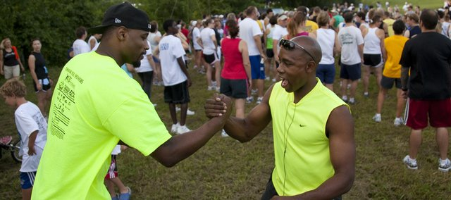 Former Jayhawk basketball players Darnell Jackson, left, and Jacque Vaughn meet up before the start of the fifth-annual Red Dog Run on Saturday along the Kansas River levee. Jackson spoke to participants and thanked them for their support of the run, which benefited the Boys and Girls Club of Lawrence. Jackson later signed autographs at Dillons to raise money for the organization.