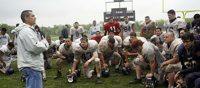 Haskell Indian Nations University football coach Eric Brock talks to his squad after its spring game. The Fightin' Indians played despite the rainy, muddy conditions at Haskell Stadium.