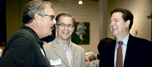 From left Brad Burnside, Lawrence, with U.S. Bank, visits with Lawrence Mayor Rob Chestnut and U.S. Sen. Sam Brownback, R-Kan., prior to Brownback's speech to members and guests of the Lawrence Chamber of Commerce Monday at Maceli's, 1031 N.H.