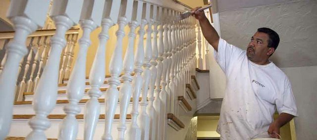 Leo Adame, of Joyce's Painting Company, touches up along the stairwell bannister at the KU chancellor's residence on Tuesday.