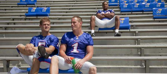 Above, Kansas University quarterback Todd Reesing, left, and running back Jake Sharp (1) take a break and visit in the Memorial Stadium stands during KU's Media Day on Tuesday. At upper right is wide receiver Dezmon Briscoe.