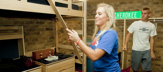 Kansas University sophomore Sarah Hicks, Bennington, searches Friday for a spot to hang her poster of country music star Taylor Swift with her younger brother Josh Hicks, 16, in Tower A of Jayhawker Towers Apartments. Renovations to Tower A involve new bedroom fixtures, kitchen appliances and kitchen fixtures.