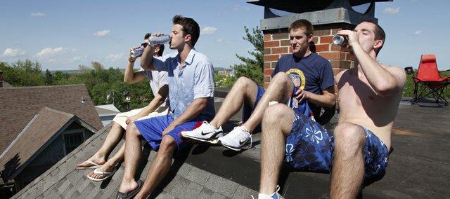Kansas University students Blair Tudas, Jeff Katz, Brad Stephenson and Lorenzo Murray lounge on a rooftop in the Oread Neighborhood during KU's Stop Day May 8.