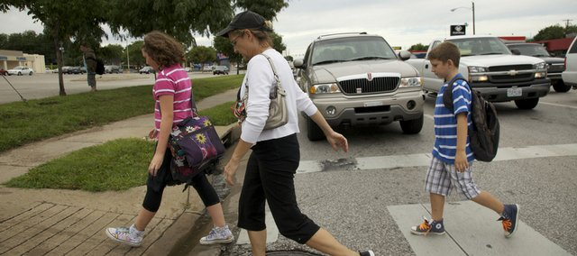 Walking back to their car almost two blocks from Schwegler School, Jackie Bird, center, crosses 23rd Street Monday afternoon with her two children, Maddie, 10, and Coltrane, 8. Bus service has been cut because of a school budget crisis, but parents are renting