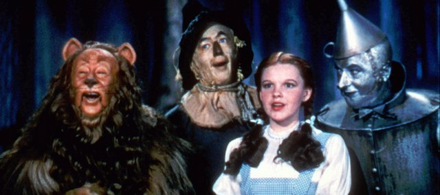 "Bert Lahr as the Cowardly Lion, Ray Bolger as the Scarecrow, Judy Garland as Dorothy, and Jack Haley as the Tin Woodman sing in this scene from ""The Wizard of Oz,"" distributed by Warner Bros. Tuesday marks the 70th anniversary of the release of the movie ""The Wizard of Oz,"" one of many repurposings of L. Frank Baum's 1900 book ""The Wonderful Wizard of Oz."""