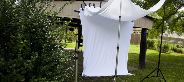 A simple and cheap photo studio can be assembled in your backyard with minimal effort. All you need are a couple of white bed sheets, some hand clamps, a little bit of strong tape and several devices for suspending the sheets.