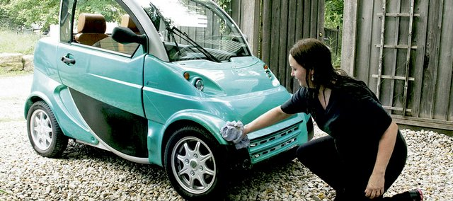 Cordelia Brown cleans up a 2004 Teener, one of 250 that were built in Italy. She and her husband, Robert, recently purchased the small neighborhood electric vehicle for $2,900. Only 26 of the tiny cars are known to be in the United States.