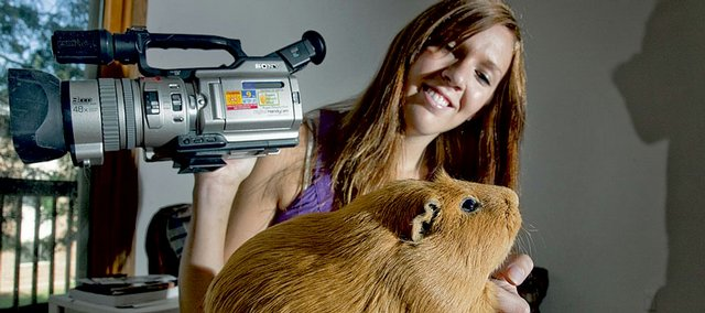 Alyssa Buecker, a Kansas University student made famous in 1999 when, as a Lawrence home school student, she was commissioned by HBO to make a movie about guinea pigs. She's pictured with Otto, a pet guinea pig.
