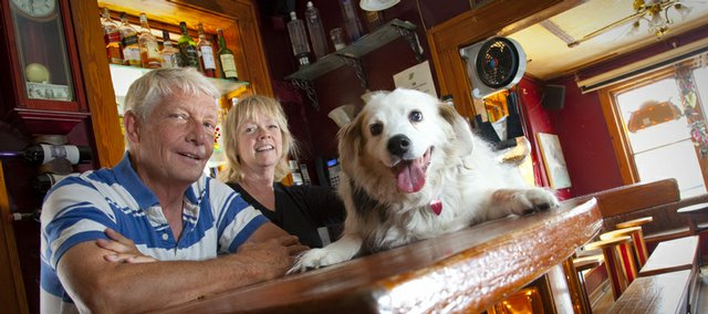 Henry's owners Dave Boulter and Sue Mee are pictured with Boulter's Australian Shepherd mix Henry, who is the namesake for the bar and coffee shop.