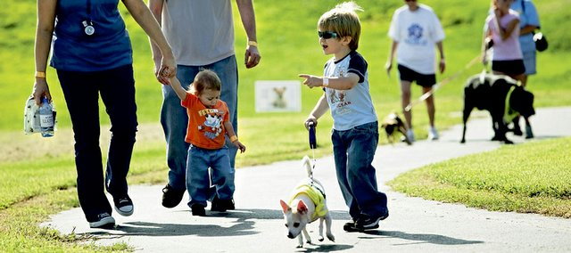 Members of the McClintock family participate Saturday in the Bark For Life event, a cancer fundraiser, in Eudora. The event was an American Cancer Society event for participants and their dogs. Saturday's relay was the first of its kind in Kansas. From left are Ellie and Tim McClintock, and their sons Kieran, 15 months, and Seamus, 3, with his dog, Frodo.