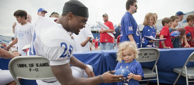 Kansas safety Darrell Stuckey returns an autographed ball to Gabby Hardy, 2, who is coach Mark Mangino's granddaughter. The players signed autographs Wednesday during Fan Appreciation Day at Memorial Stadium.