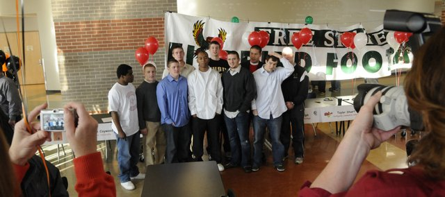 I squeezed between other photographers to shoot this group photo of Free State High School football players who signed college letters of intent in February. To improve my chances of a better exposure, I raised the ISO setting on my camera and made sure I was using a shutter speed higher than 1/30th so I would not blur the photo by shaking the camera. I positioned myself so I would get the players at center and the parents with their cameras beside me.