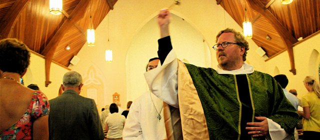 The Rev. Paul McLain waves incense at the parishioners of the Solemn High Mass at Trinity Episcopal Church, 1011 Vt. The smell of the incense aims to invoke the presence of God.