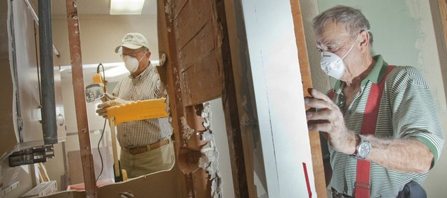 Volunteer workers Fred McElhenie, left, and Larry Rankin remove some walls Monday  during renovations to a building at 330 Maine, where Health Care Access plans to relocate from 1920 Moodie Road. The organization still needs to raise about $80,000 before moving into the new location.