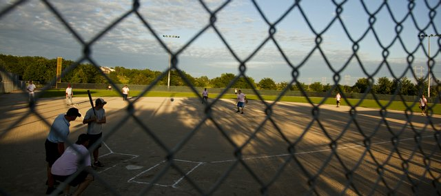 A pitch is lobbed to the plate during a game between the Kemira Phog Dogs and Those Sons of Pitches Aug. 18 at the Clinton Lake Softball Complex.