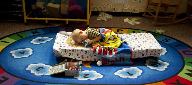 Kayden Frick plays with a Thomas the Tank Engine toy from his cot during nap time in the 4-year-old classroom at the Ballard Center in North Lawrence. Ballard Community Services, which operates a preschool and food bank, is a local organization that receives support from the United Way.