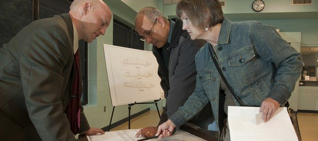 A public meeting Monday allowed residents to meet with engineers and consultants regarding the city's planned reconstruction of Kasold Drive south of Clinton Parkway. Jeff Jones, left, with Bartlett & West, explains design plans to neighbors John Martell and Billie Archer. The meeting was Monday night at the Holcom Park Recreation Center.
