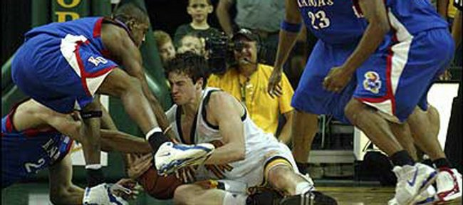 Kansas' Sasha Kaun, lower left, and Jeff Hawkins, second from left, fight Baylor's Aaron Bruce for a possession as Jayhawks Wayne Simien (23) and Aaron Miles await the outcome of the scrum.