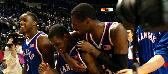 Kansas' Julian Wright, right, and Rodrick Stewart, left, walk off the court with Sherron Collins congratulating the freshman guard who led all scorers with 20 points in Monday's 71-62 win over the Wildcats at Bramlage Coliseum.