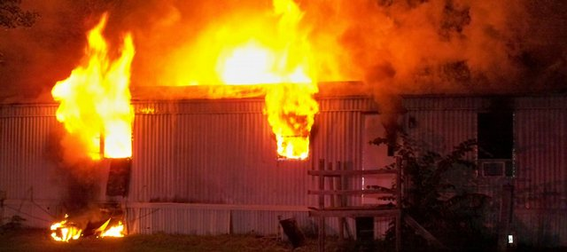 Flames rise from a trailer home Monday morning. The home, located in the Mobile Village II at 110 N. Michigan in Lawrence, sustained extensive damage. Both the home owner and his dog escaped from the structure safely. The cause of the fire is still under investigation.