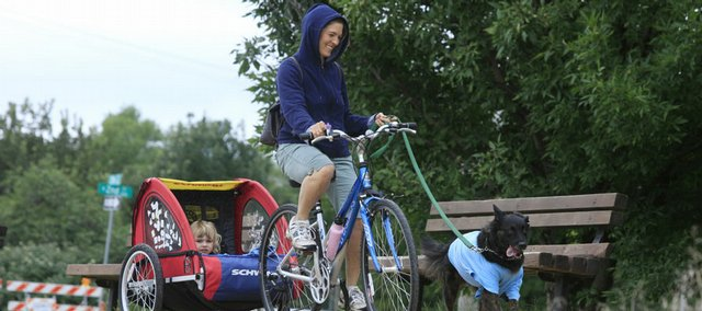 Karen Kerin ventures out in the recent chilly weather with her daughter, Summyr, and their dog, Carebear. According to Mary Knapp, state climatologist, this has been the fourth-coolest summer — June, July and August — in Lawrence in 70 years.