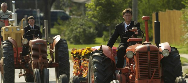 A procession of antique tractors makes a run through east Lawrence on Tuesday for the funeral of Elmer Johanning, a longtime Case farm implement dealer in Lawrence. Johanning's grandson Curtis Wakeman drove a 1954 Case D tractor that pulled a wagon carrying the casket. His brother Stuart Wakeman followed behind.