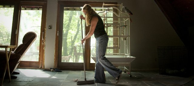Sarah Skaggs sweeps her living room floor at her home near Ozawkie. On July 9, Skaggs was laid off from her job at Line-X of Lawrence. In an effort to make the best of her unemployment, Skaggs has spent time remodeling her home.