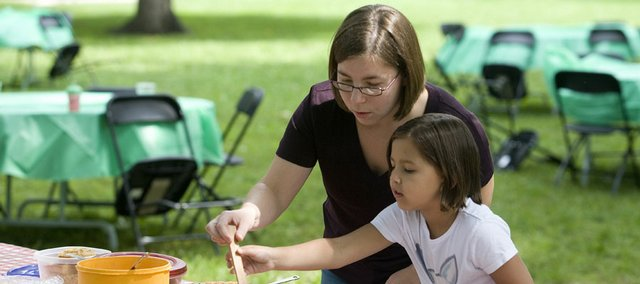 Vanessa Sanburn, Lawrence, helps her daughter, Nadia, 6, fill her plate at a potluck Monday in South Park to support the use of local produce in school lunches. Sanburn, a Lawrence school board member, said she thinks using local produce supports the local economy in addition to being generally more healthy.