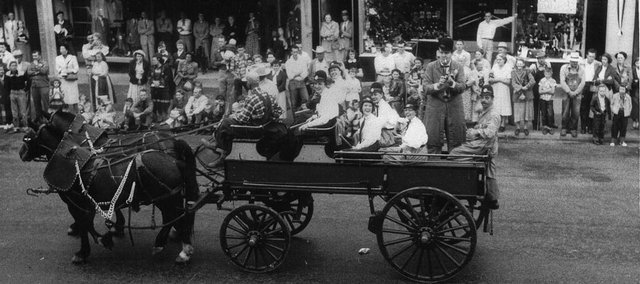 A pair horses pull this group down Mass. St. in the centennial parade in 1954. Hank Brown is playing the trumpet and Byrona Wiley and Melba Still are dressed as Keystone Kops.