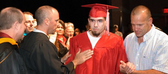 Brandon Parker, Tonganoxie High School athletics director, congratulates Austin Stone for getting his diploma. Stone, who is now blind after complications arose from medical gas he received while having his wisdom teeth removed, was helped at Tonganoxie High School by his father, Lance Stone.