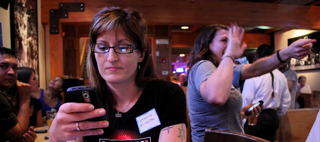 "Rikki Kite, Lawrence, tweets at the Lawrence Twestival at Joe Schmo's, 724 Mass. The event raised money for the Lawrence Humane Society. ""People think Twitter is really random and anonymous, but it's actually a great way to meet people that you have something in common with,"" says Kite, associate publisher of Linux Pro Magazine."