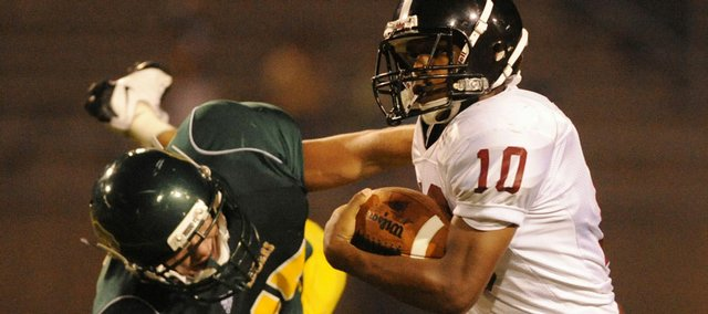 Lawrence High's Tyrae Jenkins stiff-arms a Shawnee Mission South defender. LHS lost, 28-7, Thursday at Shawnee Mission South District Stadium.