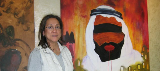 "Henri Doner-Hedrick stands next to her painting ""Blindfolded Arab,"" which was created as part of a conference on artistic reaction to the crisis in the Gaza Strip. ""My work represents all Arab leaders in the surrounding countries putting a 'blind eye' to what was happening while women, children and innocent people were being used as human shields,"" Doner-Hedrick says. ""They were waiting for Obama to be elected in hopes that the Americans would do something."""