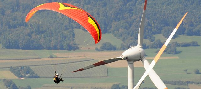 A paraglider flies past the wind turbines on the mountain of Schauinsland, southern Germany, in this AP photo that was published in Tuesday's Journal-World.