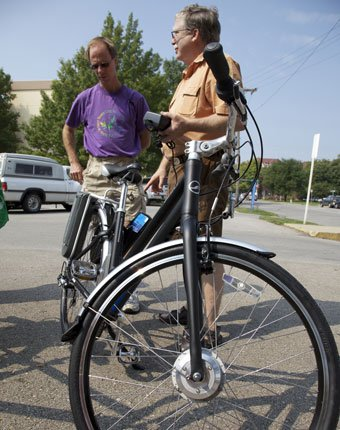 Gary Long, center, with Cycle Works, explains to Frank Schawalcer the power assist bicycle that runs on rechargeable batteries at Saturday's Lawrence Energy Conservation Fair.