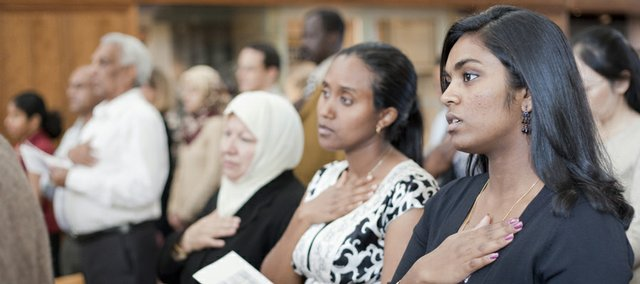 At right, Deepasaine Rajendran, from Sri Lanka, and currently a sophomore at KU in pre-med living in Overland Park, recites the Pledge of Allegiance after participating in an Oath of Citizenship during a United States naturalization proceeding Monday, Set. 14, 2009, at the Dole Institute. Rajendran was one of 99 people who became U.S. citizens during the ceremony.