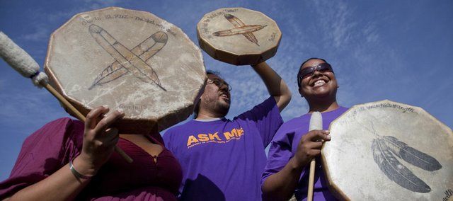 Marei Spaola, a Haskell Indian Nations University senior, Oglala Lakota, center, and Temeka Circle Bear, HINU sophomore, a Cheyenne River Sioux, both from Rapid City, S.D., participate in an opening drum ceremony Thursday at Haskell Stadium. Haskell is celebrating its 125th anniversary this year, and Thursday marked the exact date 125 years ago that the school was opened.