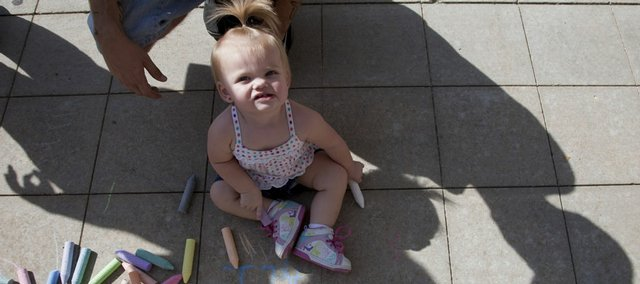"Alessandra Marks, 1, plays with chalk in the shadow of her father, Brandon Marks, Tonganoxie, in 2009 at the ""Kickin' it with WIC"" event at the Community Health Facility, 200 Maine. The 2011 event will be Thursday."