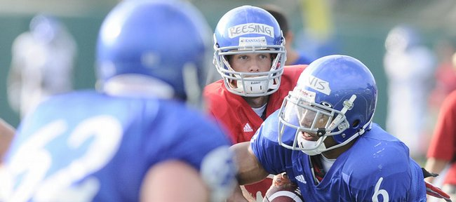 Kansas quarterback Todd Reesing hands off to running back Rell Lewis during practice Tuesday, Aug. 11, 2009 at the practice fields adjacent to Memorial Stadium. Lewis could see playing time in KU's game against Southern Miss.