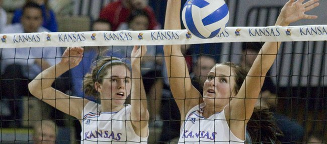 KU players Nicole Tate, left, and Paige Mazour, right, attempt to block an Oklahoma shot at the net Wednesday in KU's five-set victory.