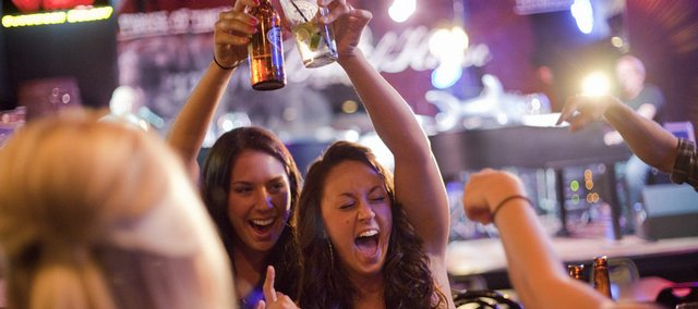 A table of Kansas University students celebrate a night out and sing along with the live music during Ladies' Night at The Barrel House, 729 N.H.