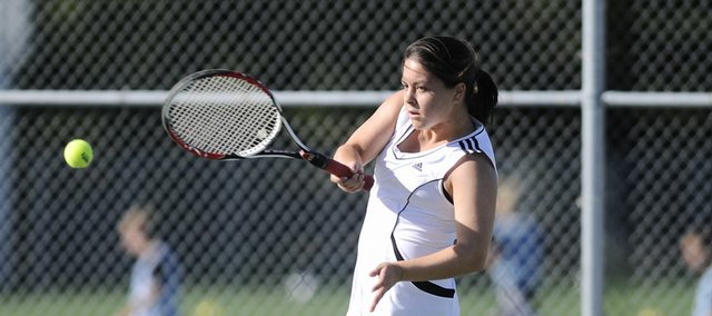 Lawrence High senior Jordan Payne returns a serve during the No. 1 doubles match against Free State. Payne and teammate Elizabeth Simons won their match, and the Lions beat the Firebirds, 5-4, Monday at FSHS.