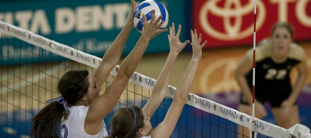 Kansas Universitys Paige Mazour (8) and Nicole Tate (13) block a Colorado shot near the net. The Jayhawks held off the Buffaloes, 3-1, on Wednesday at Horejsi Center.