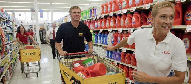 Toni Martin, Lawrence, right, runs through the Sixth Street Hy-Vee store, leading NASCAR driver Clint Bowyer, driving the grocery cart, center, on a two-minute, 33-second shopping spree Thursday. Hy-Vee and General Mills matched the $1,000 in merchandise collected by Martin and Bowyer and donated $500 each to ECKAN Just Food and LINK.