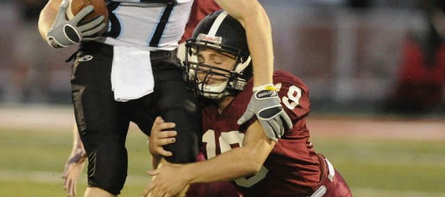 Lawrence High defender Jonathan Pederson tries to keep a grip on Shawnee Mission East wide receiver Kevin Hertel.