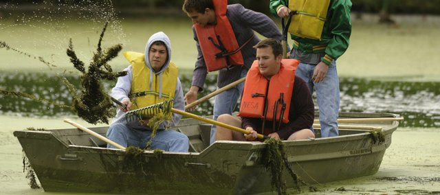 From front left, Adam Hope, Blake Warner, rear left, Alex Belot and Sam Hagen, all members of the Delta Upsilon fraternity, pull rakes through the water at Potter Lake as part of a cleanup effort Saturday. The Potter Lake Project spearheaded the effort.