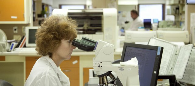 Chris Knowles, a medical technician and head of the hematology section, views a sample through a microscope in October 2009 in the laboratory at Lawrence Memorial Hospital.